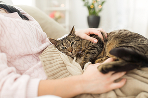 pets, hygge and people concept - close up of female owner with tabby cat in bed at home