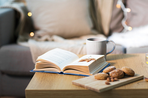 hygge and cozy home concept - book with autumn leaf, cup of tea and oatmeal cookies on wooden table