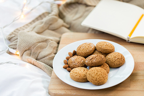 food, bakery and hygge concept - oatmeal cookies on wooden board at home