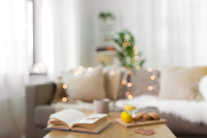 hygge and cozy home concept - blurred background of living room with book, cup of tea and food on table and sofa