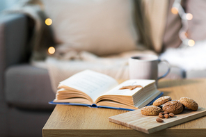 hygge, bake and food concept - oatmeal cookies, almonds, book and tea on wooden table at home