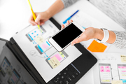 app design, technology and business concept - web designer or developer with smartphone working on user interface and drawing sketches at office