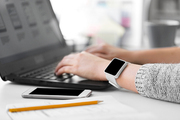 app design, technology and business concept - designer with smart watch and laptop at office