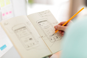 technology, user interface design and people concept - hand of ui designer or developer drawing smartphone sketches in notebook at office