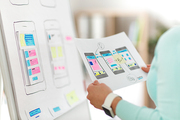 technology, user interface design and people concept - hand of ui designer or developer with smartphone app templates and flip chart working at office