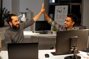 deadline, teamwork and success concept - creative team with computers making high five at night office