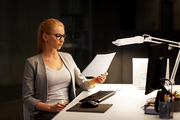 business, deadline and technology concept - businesswoman with papers and computer working at night office