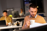 business, overwork and people concept - happy male office worker drinking coffee
