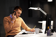 business, deadline and technology concept - businessman with notepad calling on sartphone at night office