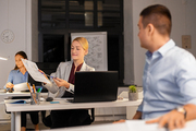 business, deadline and technology concept - woman showing charths to colleague late at night office