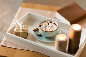 hygge, decoration and christmas concept - candles burning in lanterns and festive garland on window sill at home