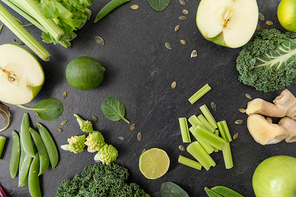 food, culinary and healthy eating concept - close up of different green vegetables and fruits on slate stone background
