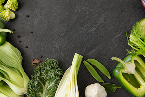 food, culinary and healthy eating concept - close up of different green vegetables on slate stone background
