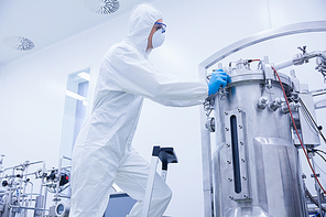 Scientist in protective suit standing on ladder