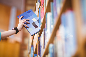 Students hand with smartwatch picking book from bookshelf at the university