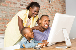 Casual smiling family on a computer in living room