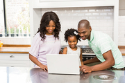 Happy family using laptop in the kitchen
