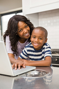 Mother and son using laptop in the kitchen
