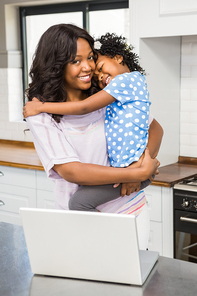 Mother using laptop while carrying kid in kitchen