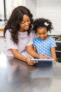 Happy mother using a tablet pc with her daughter