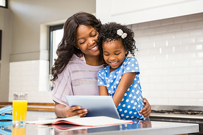 Mother and daughter using tablet in the kitchen