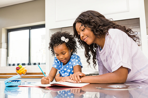 Young girl doing her homework with her mother in the kitchen