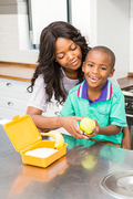 Smiling mother preparing sons school lunch in the kitchen