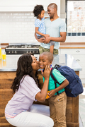mother kissing her son going to school in the kitchen