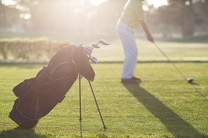 Golf bag with man in background during sunny day