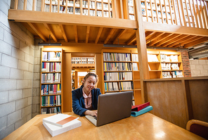 Young woman reading book in library at college