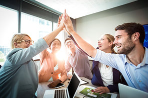 Business people giving high five at desk in the office