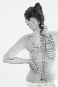 Digital composite of highlighted spine of woman with back pain at home