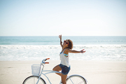 Side view of beautiful African american woman riding bicycle with arms outstretched on the beach
