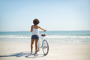 Rear view of African american woman walking with bicycle on the beach