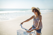 Side view of beautiful African american woman with bicycle at beach on a sunny day
