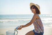 Side view of happy African american woman riding a bicycle at beach on a sunny day