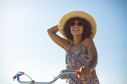 Low angle view of happy African american woman with bicycle at beach on a sunny day