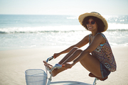 Side view of beautiful African american woman riding a bicycle with her legs on handlebar at beach