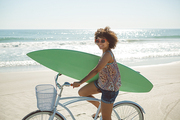 Front view of beautiful African american woman holding a surfboard with bicycle at beach