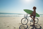Side view of African american woman holding a surfboard with bicycle at beach on a sunny day