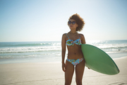 Front view of beautiful African american woman standing with surfboard on the beach