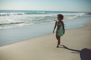 Front view of beautiful African american woman walking with surfboard on the beach
