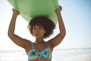 Front view of beautiful African american woman carrying surfboard on her head at beach