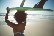 Rear view of African american woman carrying surfboard on her head at beach