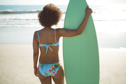 Rear view of African american woman standing with surfboard on the beach