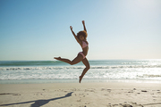 Front view of beautiful African american woman jumping at beach on a sunny day
