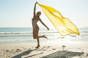 Front view of beautiful African american woman in swimwear waving yellow scarf on the beach