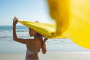 Rear view of beautiful mixed race woman in swimwear waving yellow scarf on the beach