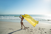 Rear view of mixed race woman in swimwear waving yellow scarf on the beach