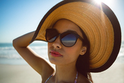 Front view of beautiful mixed race woman in hat and sunglasses standing on the beach